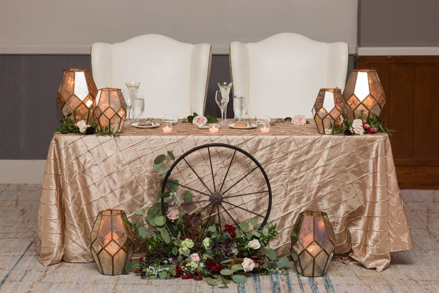 The sweetheart table by Petal Pushers with a light gold patterned table covering, unique multicolored candle holders, various florals and a wagon wheel