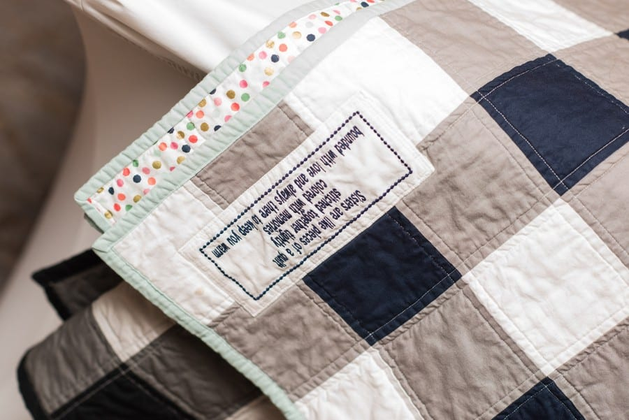 A close up of a personalized quilt used as a guest sign in at the wedding