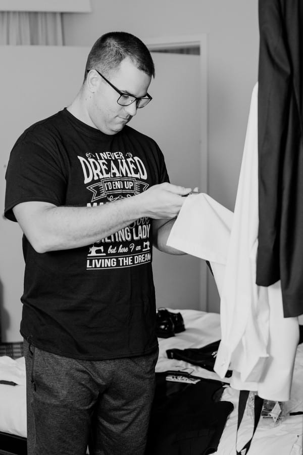 Black and white candid of the groom checking out his tuxedo before putting it on