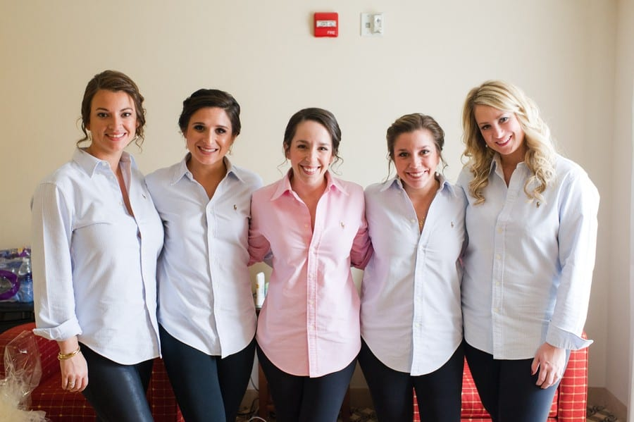 The bride in a pink oxford shirt with her bridal party in white oxford shirts