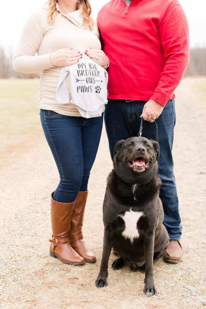 3/4 photo of Mom and Dad to be with black lab pup, focus on the dog and the custom onesie