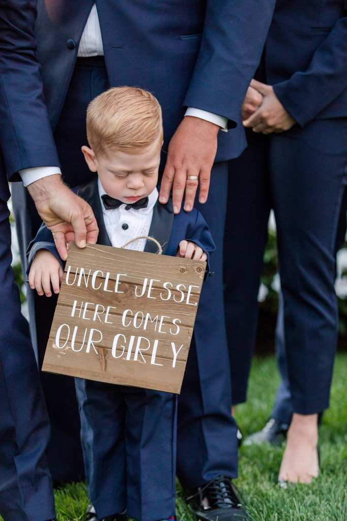 Close up of a ring bearer holding custom signage while standing with the grooms people