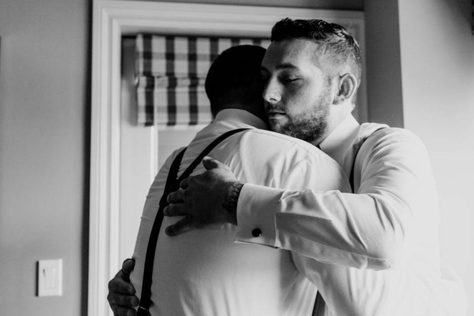 Black and white candid photo of the groom hugging a groomsman