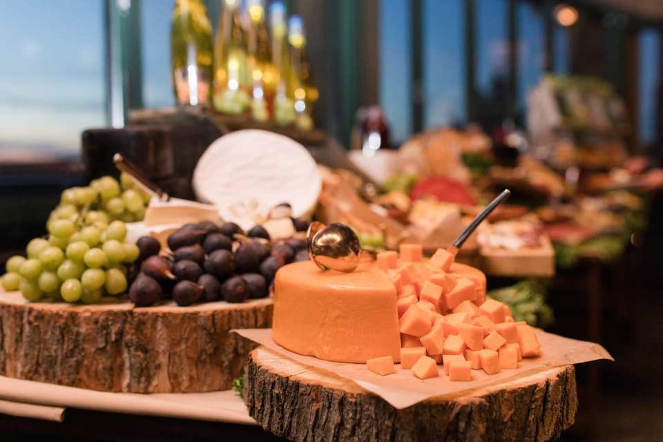 Various cheeses and fruits on display on cut wooden log pieces during the cocktail hour at the Grand Cascades Lodge at Crystal Springs Resort