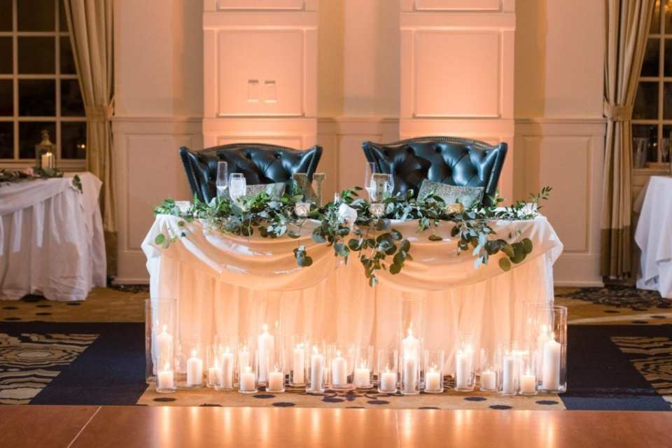 Sweetheart table decorated in greens and candles by Added Touch Florist at the Grand Cascades Lodge at Crystal Springs Resort