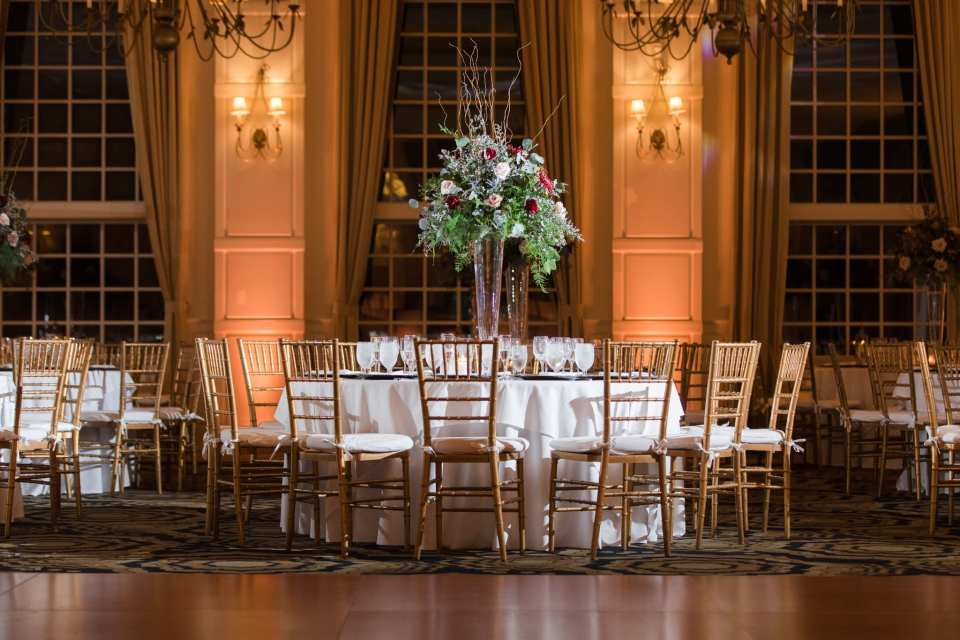 Focus on a table in the ballroom at the Grand Cascades Lodge at Crystal Springs Resort decorated with classic gold chivari chairs, ivory table linens, and tall floral arrangement with an abundance of greenery and roses in blush and red by Added Touch Florist