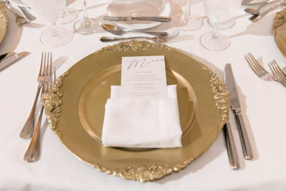 Place setting with gold charger with custom menu card in cloth napkin displayed on top
