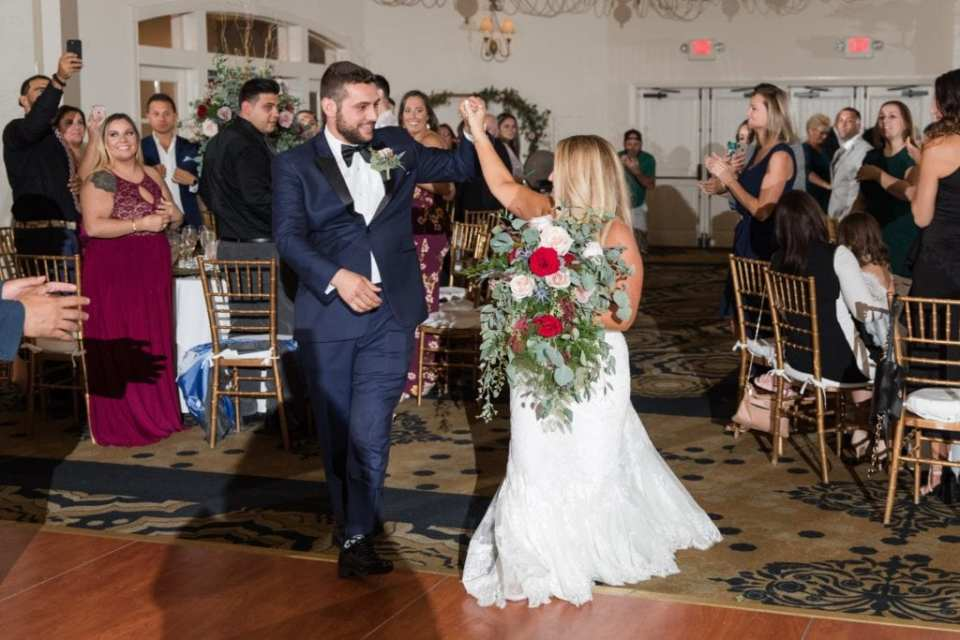 The bride and groom make their grand entrance into their wedding reception at the Grand Cascades Lodge at the Crystal Springs Resort. Brides bouquet of blush and red florals with large amounts of various greenery by Added Touch Florist