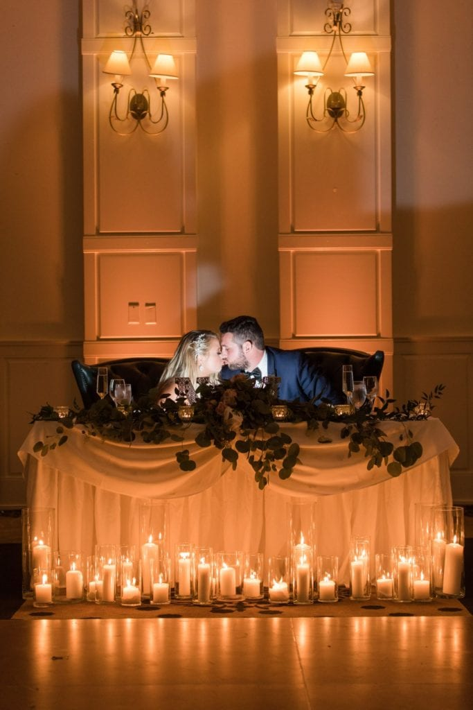 Bride and groom share a kiss at their sweetheart table decorated in greens and candles by Added Touch Florist at the Grand Cascades Lodge at Crystal Springs Resort