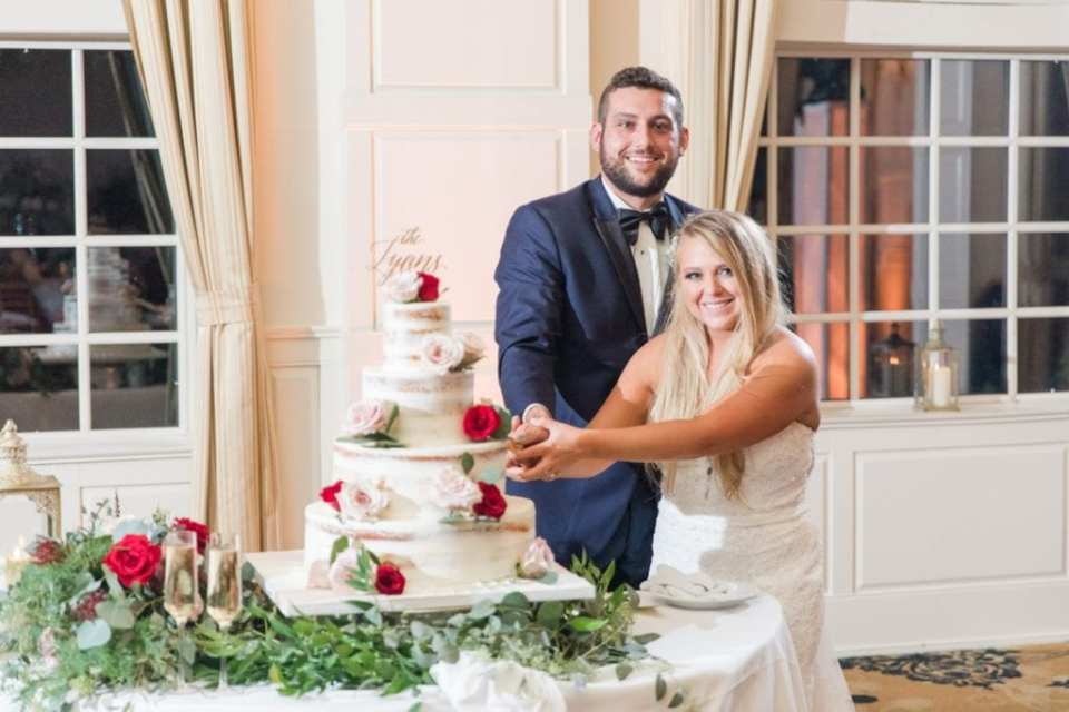 Bride and groom cut their four tier semi naked cake with custom gold cake topper