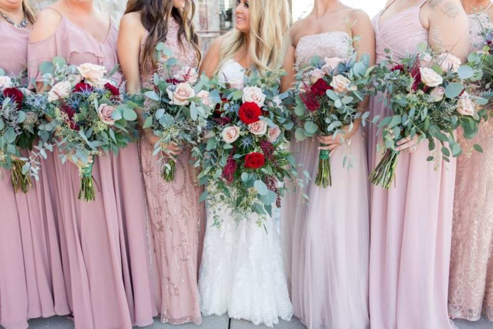 Focus on the bridal party in pink gowns from Bella Bridesmaids and their bouquets of red and blush florals, with added greenery by Added Touch Florist