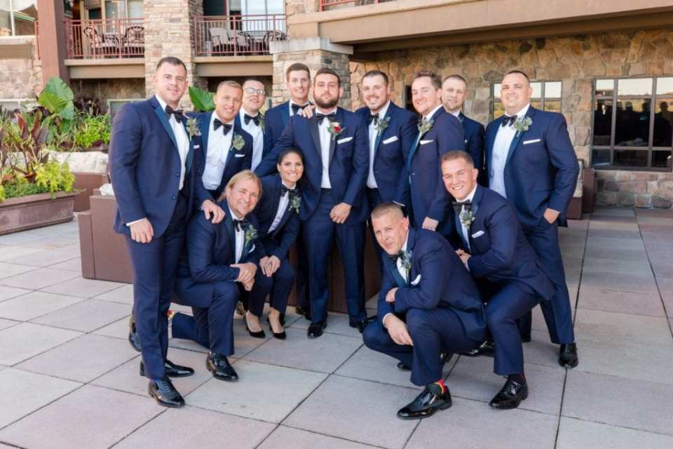 The groom and his groomspeople in navy blue and black tuxedos by Chazmatazz