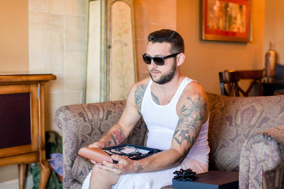 The groom in sunglass and a white undershirt opening a gift from his bride