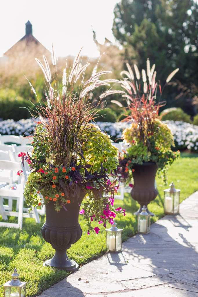 Close up of aisle decor including glass candle lanterns and a mix of wildflowers and foliage in urns on display in the outdoor ceremony area at the Grand Cascades Lodge at Crystal Springs Resort