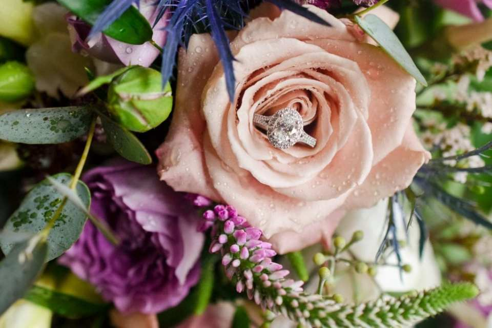 The brides oval diamond engagement ring with diamond halo placed in a dusty rose colored rose within the bridal bouquet by Ross Plants & Flowers