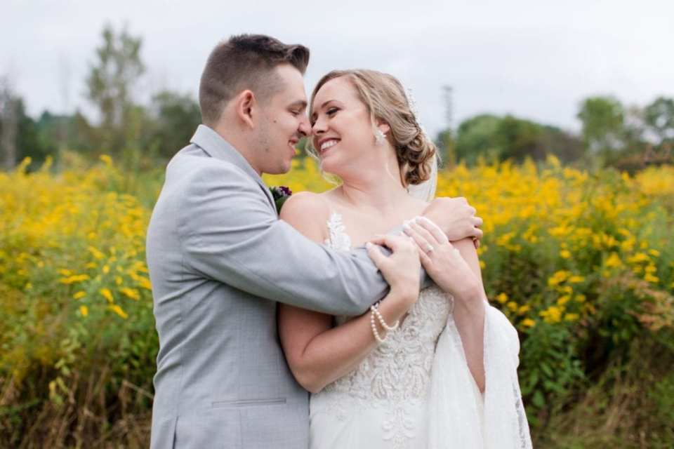 Bride and groom, nose to nose, embrace outdoors in front of a field of yellow wildflowers