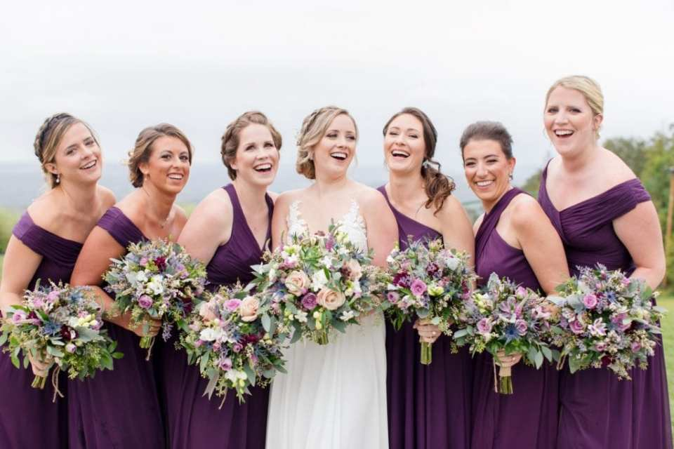 Fun photo of the bride in her Allure bridal gown and her bridemaids in a purple off the shoulder gown by David's Bridal holding a bouquet of wildflowers by Ross Plants & Flowers in these Blue Mountain Resort Wedding photos