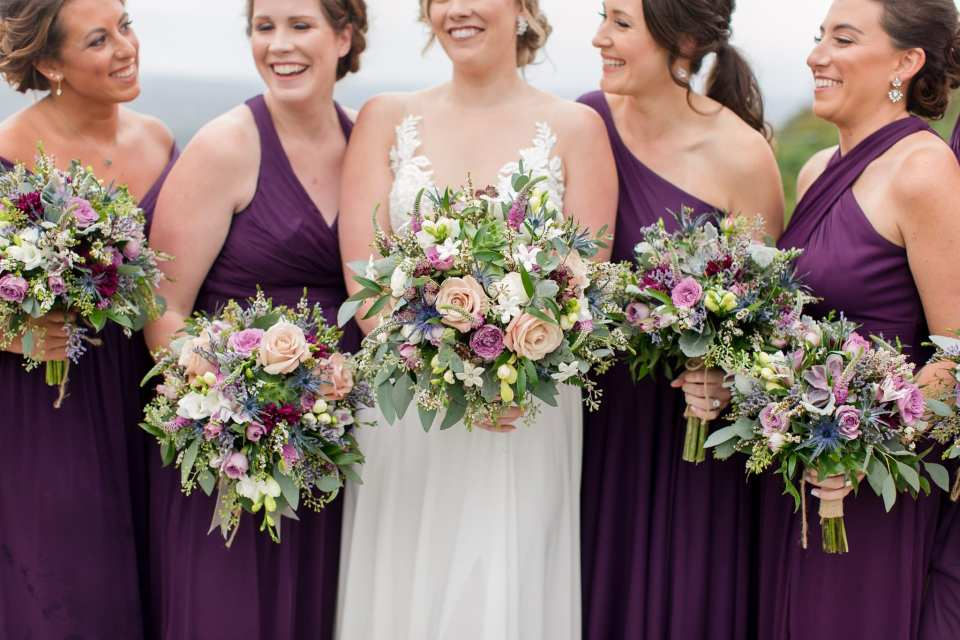 Close up of the bride in her Allure bridal gown and her bridemaids in a purple off the shoulder gown by David's Bridal holding a bouquet of wildflowers by Ross Plants & Flowers in these Blue Mountain Resort Wedding photos