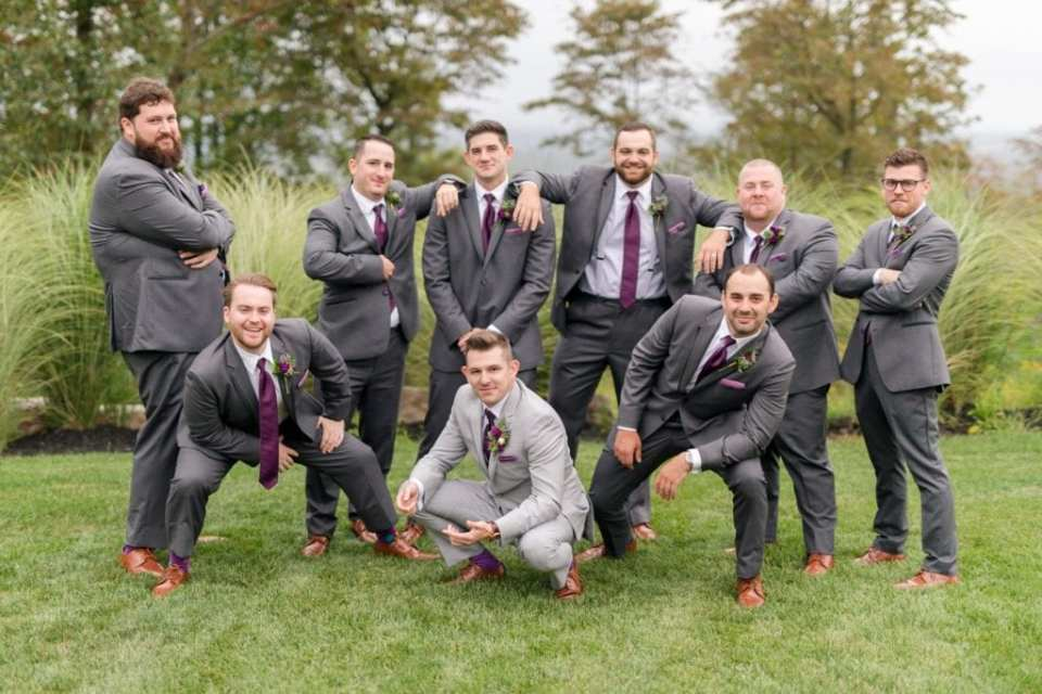 A fun groom with his groomsmen photo in suits of different shades of grey by Mens Wearhouse