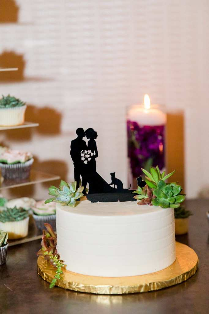 Small white one tier wedding cake with a black silhouette of a bride and groom on top with a few succulents to decorate