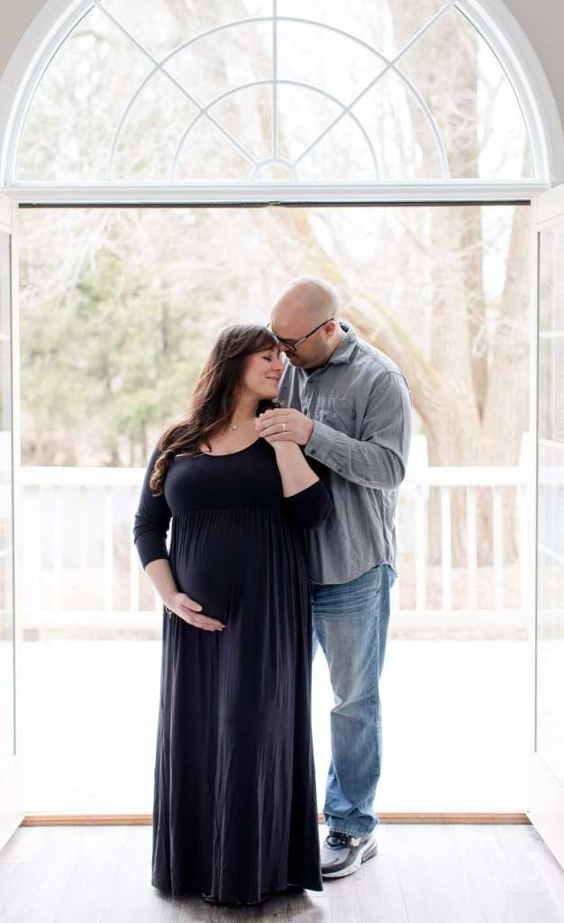 Dad to be behind the mother to be, she looks down peacefully in these New Jersey maternity photos