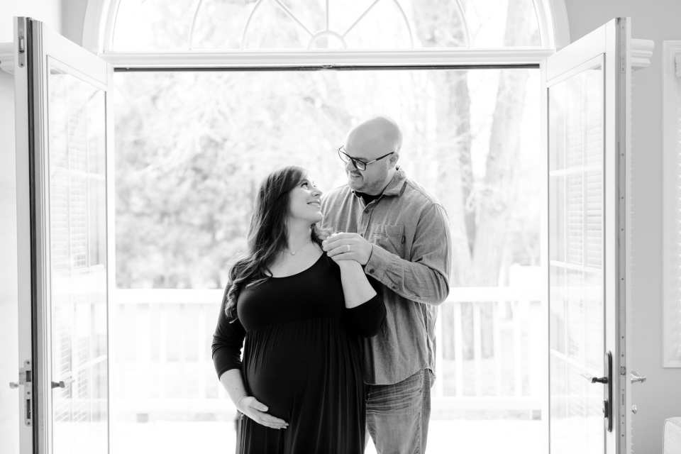 Black and white shot of Dad to be behind the mother to be, she looks up at his, peacefully in these New Jersey maternity photos