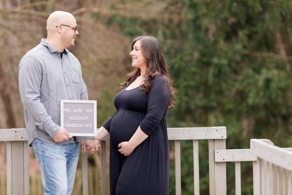 Dad and Mom to be hold hands, while looking at each other. A custom sign addressed to their unborn son is in between them