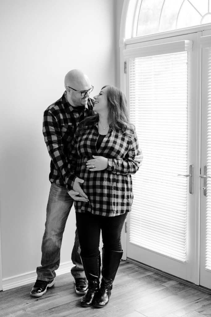 Black and white shot of Dad to be behind the mother to be, she looks up at his face, peacefully in these New Jersey maternity photos