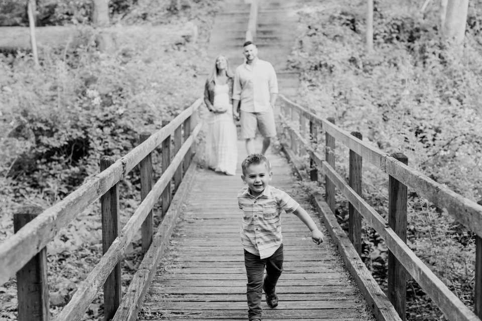 Black and white candid photo of little boy running on wooden bridge at Allaire State Park with parents behind him walking at a distance
