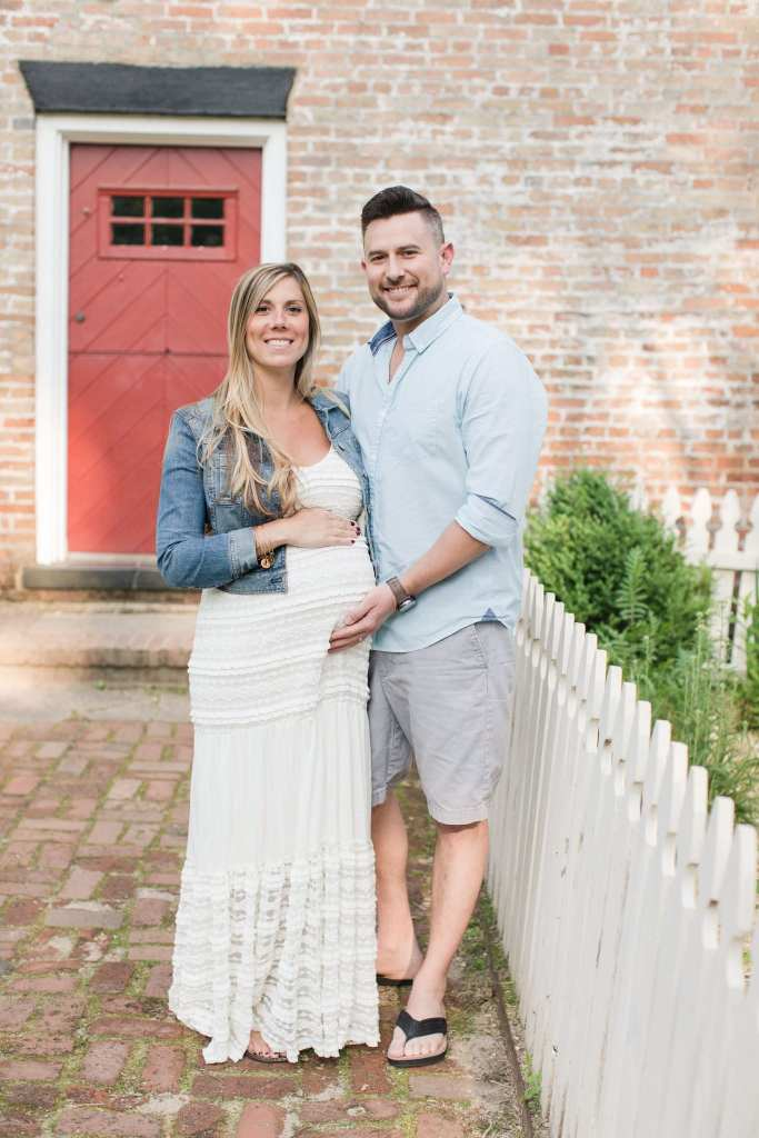 Portrait of pregnant couple in front of historic brick building. Maternity photos in NJ