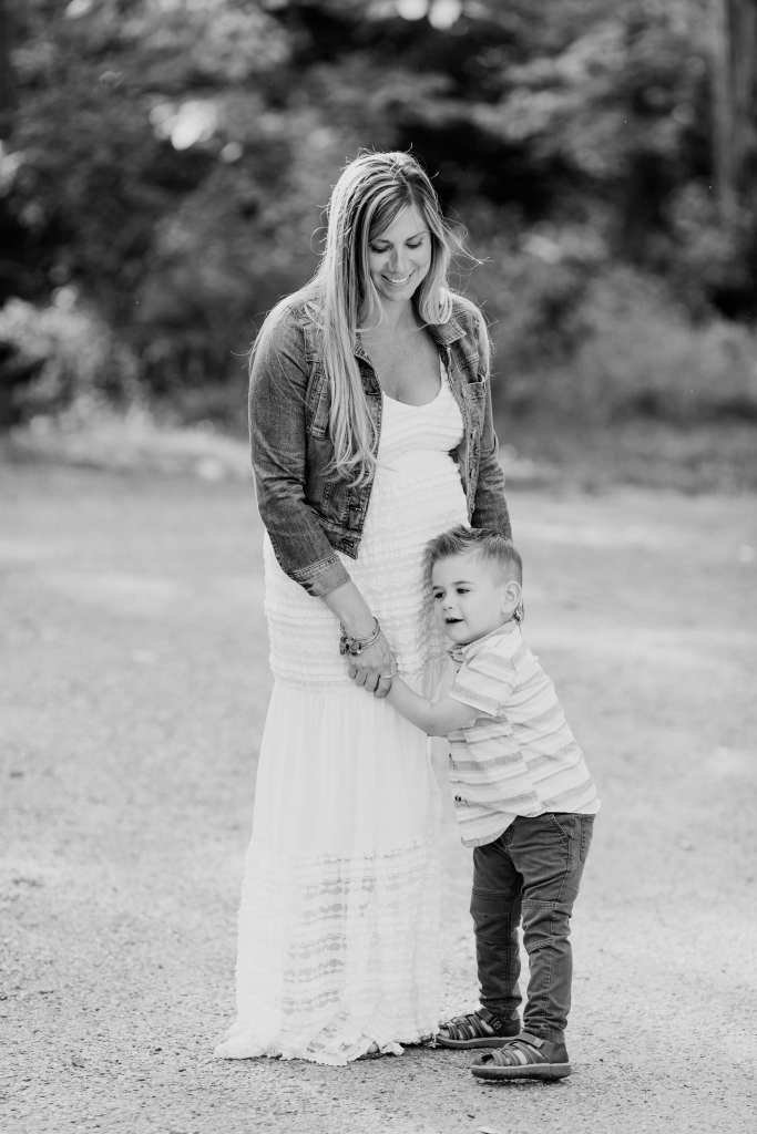 Black and white of small son leaning into Mom's pregnant belly