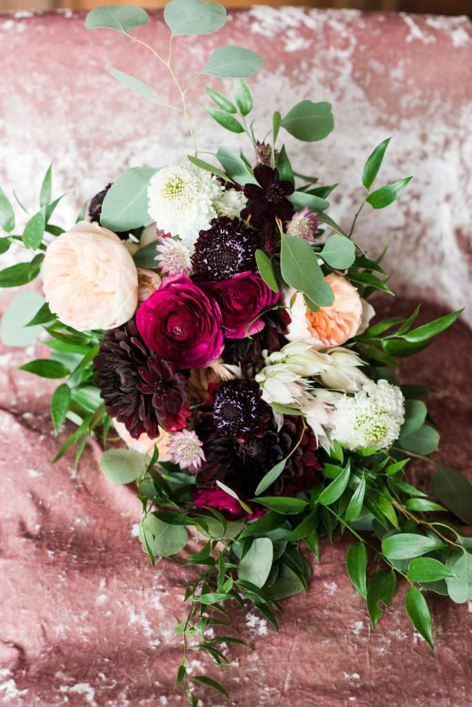 Bouquet of blush, dark red, dark pink and greens by Whisper and Brook Flower Company