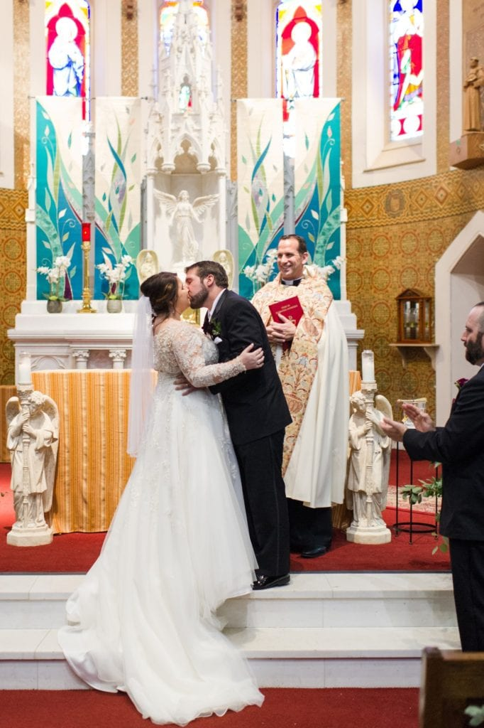 The groom kisses his bride at the end of the ceremony at St Joseph's Thrift Shop