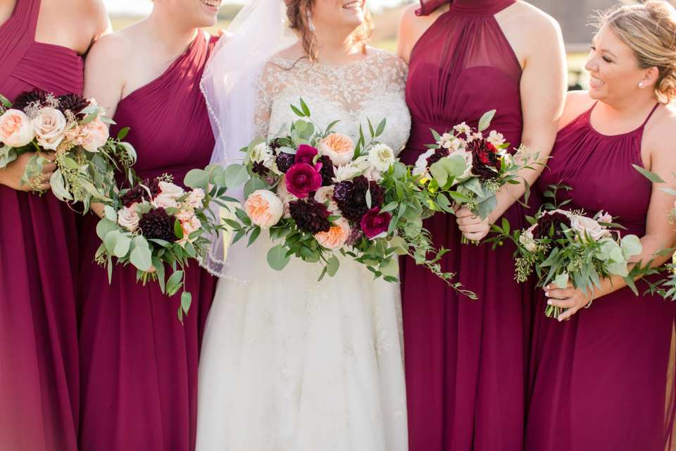 Photo of bride in Justin Alexander and the bridal party in wine colored gowns by Azazie, with the focus on the bouquets at waist height, by Whisper and Brook Flower Company