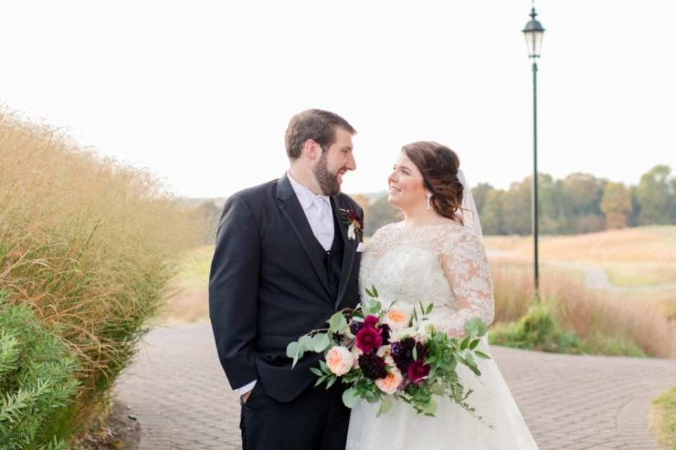 Formal portrait of the bride and groom, both gazing at one another, her bridal bouquet by Whisper and Brook Flower Co. prominently displayed Ballyowen Golf Course in background