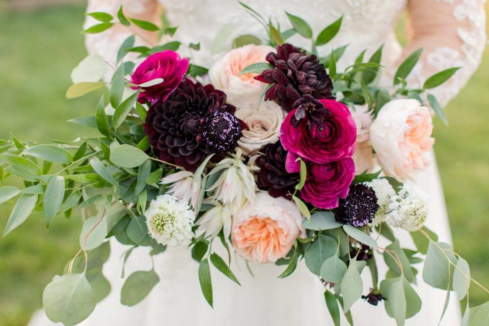 Dark red, light red, pink, blush, cream colored florals in loose bouquet by the Whisper and Brook Flower Company
