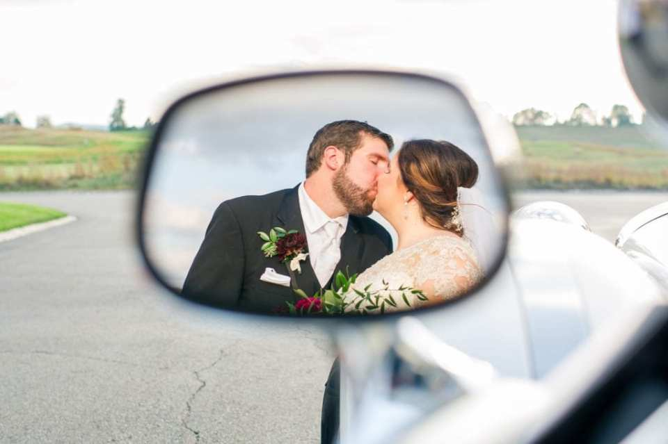 Photo of reflection of bride and groom kissing in the side view mirror of the antique car from Moonlight Limo Service used to transport the bride and groom from the church to Ballyowen Golf Club for their reception