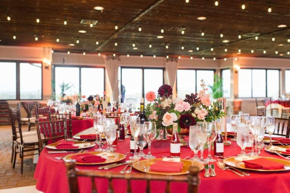 Unique shot of the reception decorated in dark wood chivari chairs, cream and dark red linens and low floral arrangements in these Ballyowen Golf Club wedding photos