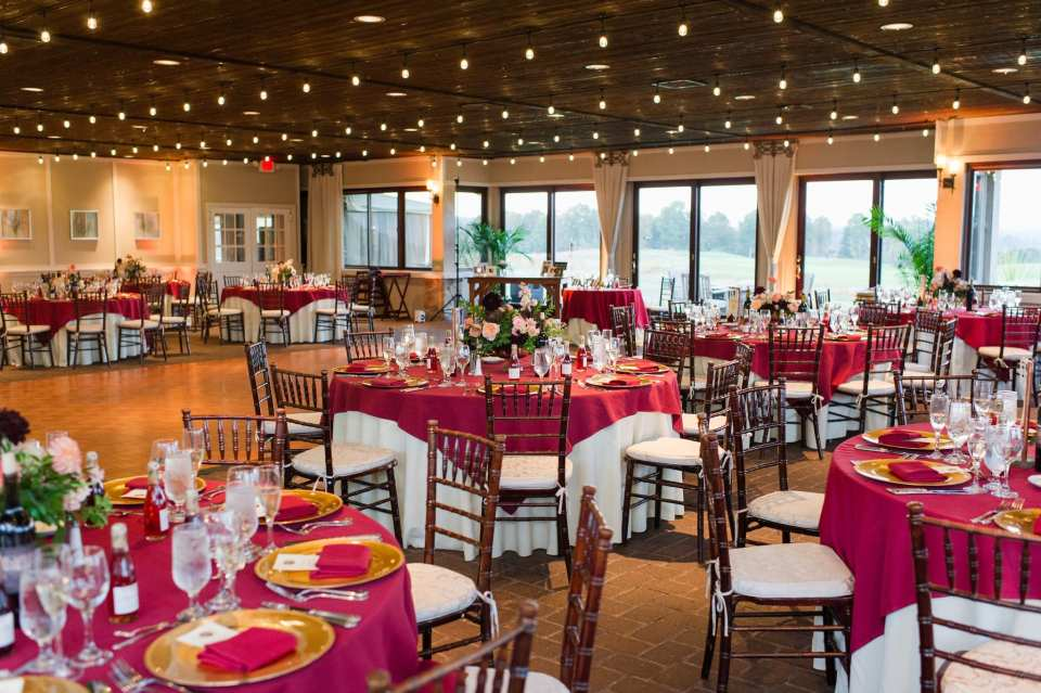 Wide angle shot of the reception decorated in dark wood chivari chairs, cream and dark red linens and low floral arrangements in these Ballyowen Golf Club wedding photos