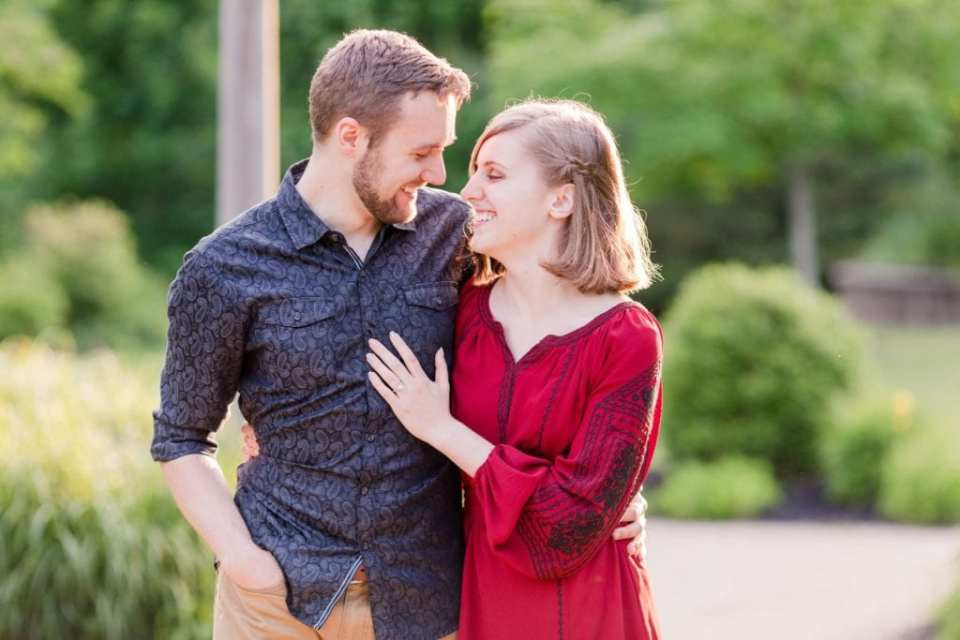 Couple walking with arms wrapped around one another, laughing and smiling at one another in their Sayen Gardens Engagement Photos