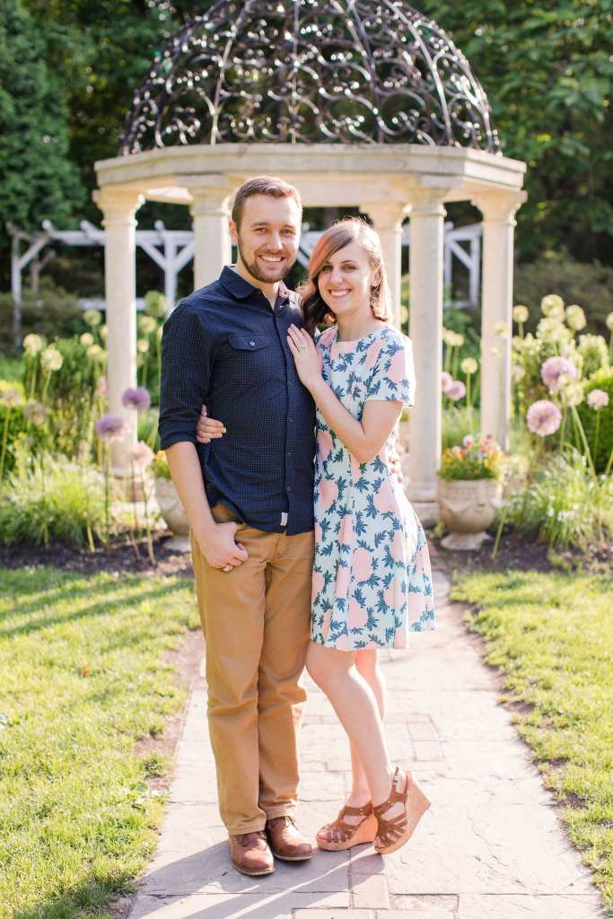Formal standing engagement photo of couple in front of stone gazebo in the Sayen Gardens