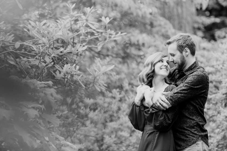 Black and white shot of couple from behind branches: he has his arms wrapped around her upper body, her hands on his arms in these Sayen Gardens Engagement Photos