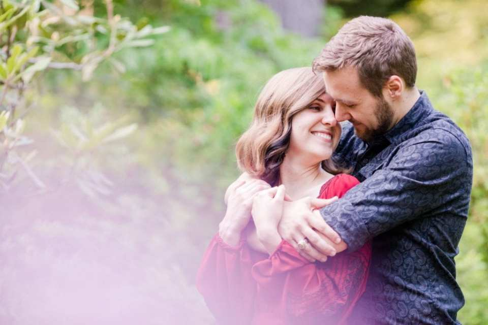 Shot of couple from behind branches: he has his arms wrapped around her upper body, her hands on his arms in these Sayen Gardens Engagement Photos