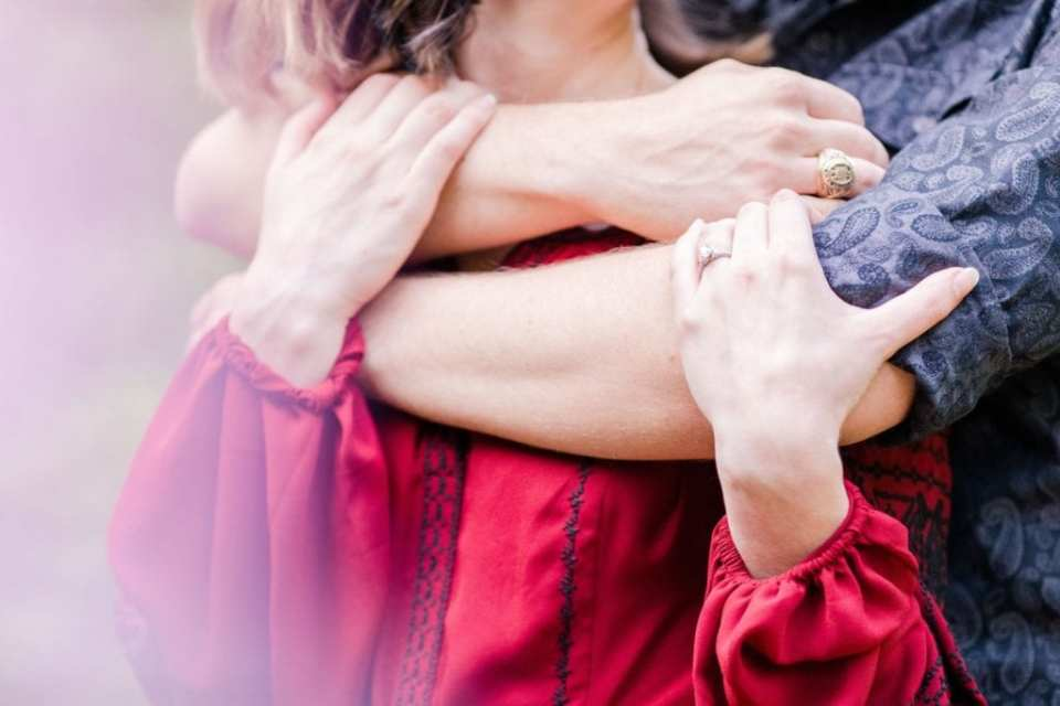 Zoom in on couple: he has his arms wrapped around her upper body, her hands on his arms, the engagement ring in focus