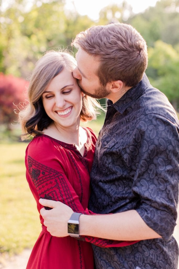 Engaged couple embracing, he is kissing her temple while she looks away