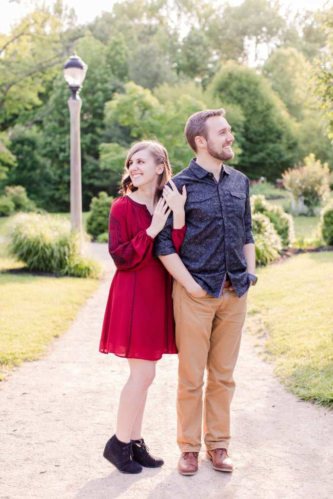 Couple, standing, looking opposite directions, her left hand on his bicep with engagement ring on display in these Sayen Garden Engagement Photos