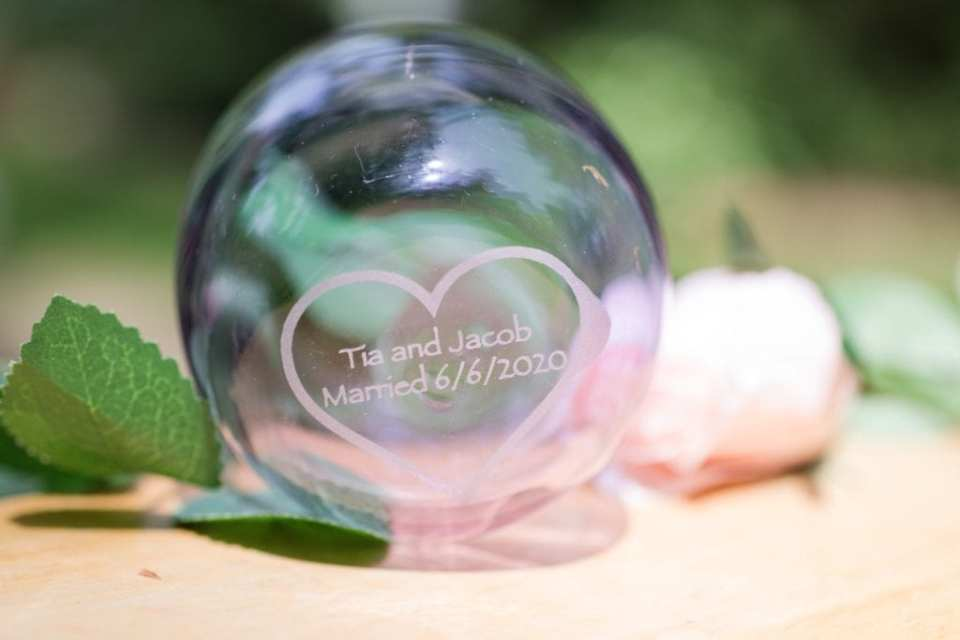 Close up of a wedding detail: a glass globe, customized with the bride and groom's names and date of wedding, custom made by JM Glass Co.