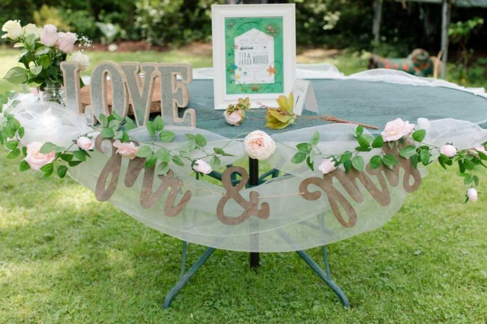 The wrought iron outdoor table being used as the sweetheart table; decorated with tulle, carved wooden phrases, florals in light pink and cream, and framed signage