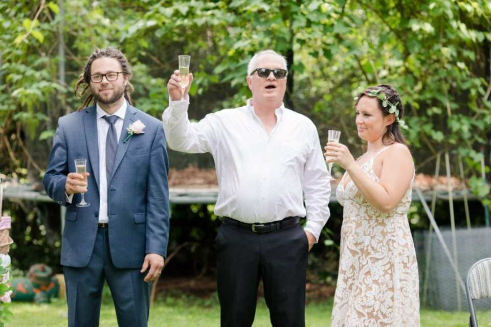 The father of the groom, flanked by the bride and groom, raises a glass of champagne during a toast
