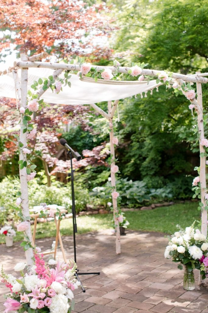 The white birch wood chuppah with floral accents in all shades of pink